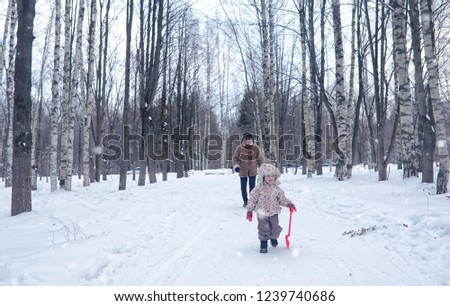 Kid running in a winter park and have fun with family #1239740686