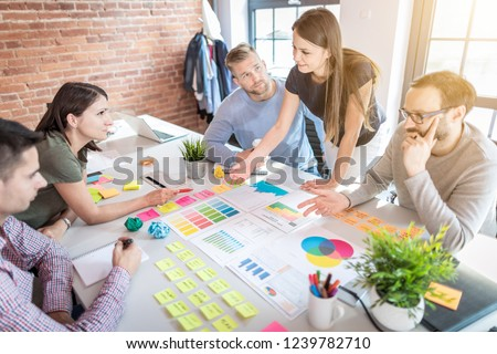 Business people meeting at office and use post it notes to share idea. Brainstorming concept. Sticky note on glass wall. #1239782710