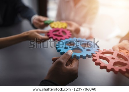 Business team connect pieces of gears. Teamwork, partnership and integration concept #1239786040