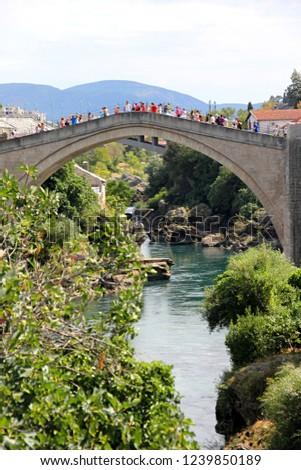 Mostar,Bosnia and Herzegovina august 22, 2016: The Old bridge in Mostar (Stari Most bridge) in a beautiful summer day and Neretva river, Bosnia and Herzegovina #1239850189