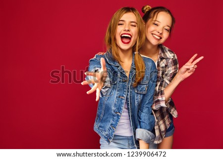 Two young beautiful blond smiling hipster girls posing in trendy summer checkered shirt clothes. Carefree women isolated on red background. Positive models going crazy and hugging #1239906472