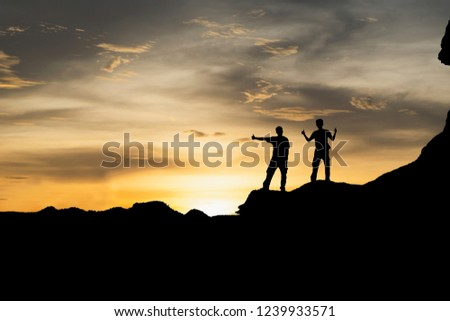 Silhouette two men standing on the mountain with a happy expression,People top on a mountain. #1239933571