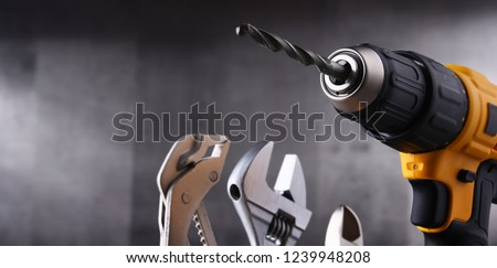 Composition with hardware tools including cordless drill and monkey spanner #1239948208