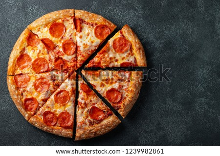 Tasty pepperoni pizza and cooking ingredients tomatoes basil on black concrete background. Top view of hot pepperoni pizza. With copy space for text. Flat lay #1239982861