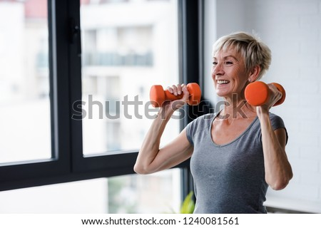 Portrait of senior woman lifting dumbbells Royalty-Free Stock Photo #1240081561