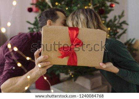 Happy couple kissing near the decorated Christmas tree and holding gift with red ribbon. #1240084768