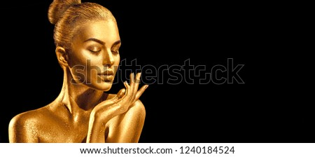 Gold Christmas Woman. Beauty fashion model girl with Golden make up, hair and jewellery, pointing hand on black background. Gold glowing skin. Metallic, glance Fashion art portrait, Hairstyle, make up #1240184524