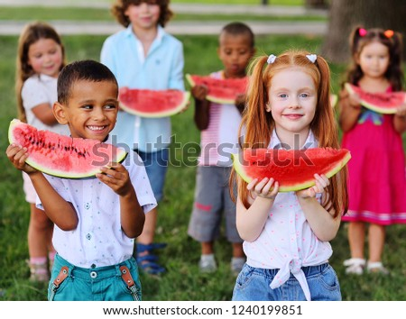 a large group of happy preschool children of different ethnic types are holding slices of ripe watermelon and smiling at the background of the Park on a Sunny summer day. #1240199851