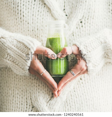 Winter seasonal smoothie drink detox. Female in sweater holding bottle of green smoothie or juice making heart shape with her hands, square crop. Clean eating, weight loss, healthy dieting food #1240240561