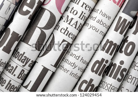 Newspaper headlines shown side on in a stack of daily newspapers Royalty-Free Stock Photo #124029454