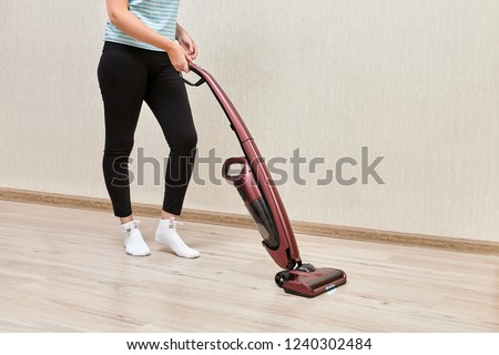 Cleaning woman in black leggins is vacuuming with help of upright vacuum cleaner with led lights on. #1240302484