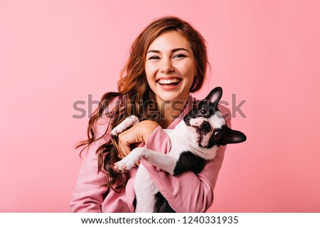 Wonderful european female model chilling in studio with puppy. Indoor portrait of debonair girl enjoying photoshoot with her cute pet. #1240331935