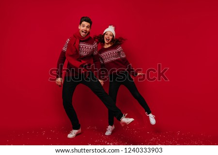 Couple in new year sweaters dancing on red background. Studio full-length shot of positive young people having fun during christmas photoshoot.