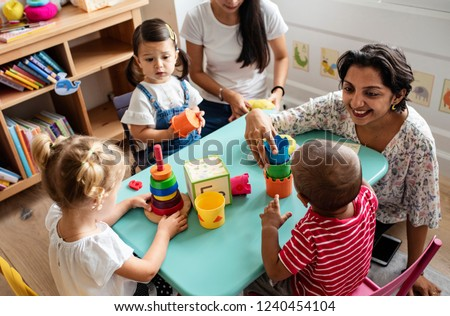 Nursery children playing with teacher in the classroom Royalty-Free Stock Photo #1240454104