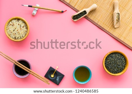 Chinese traditional symbols concept. Tea, rice, hieroglyph love, bambootabe mat, chopsticks, soy sause on pink background top view frame copy space #1240486585