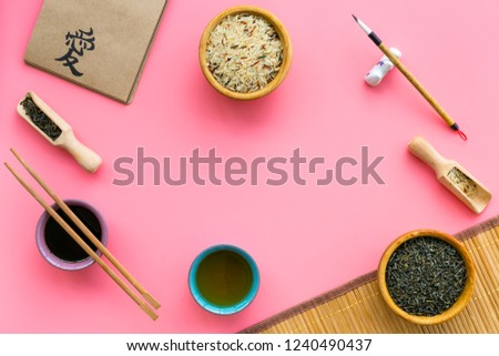 Chinese traditional symbols concept. Tea, rice, hieroglyph love symbol, bambootabe mat, chopsticks, soy sause on pink background top view frame copy space #1240490437