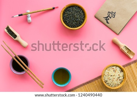 Chinese traditional symbols concept. Tea, rice, hieroglyph love symbol, bambootabe mat, chopsticks, soy sause on pink background top view frame copy space #1240490440