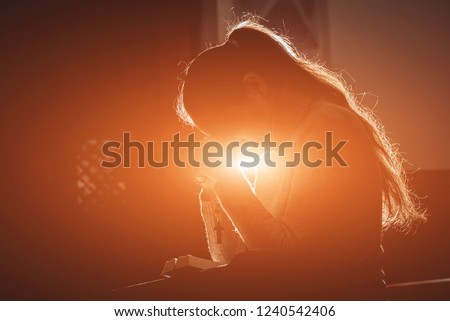 Christian woman praying in church. Hands crossed and Holy Bible on wooden desk. Background #1240542406