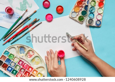 collection of accessories for artists. Canvas, oil paint tube, artistic brushes, palette, and hand with a brush lying on a blue table. Artist master background. Flat lay top view. #1240608928