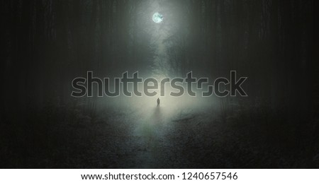Surreal horror scene with alone strange man in dark night forest. Dreamy landscape. Royalty-Free Stock Photo #1240657546