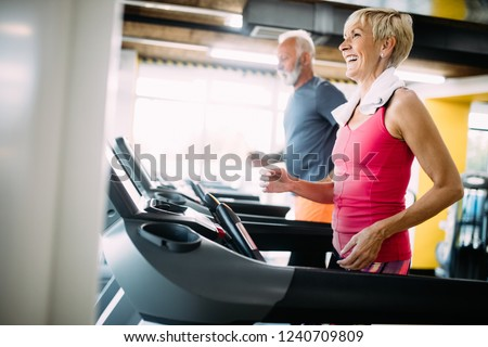 Senior people running in machine treadmill at fitness gym club #1240709809