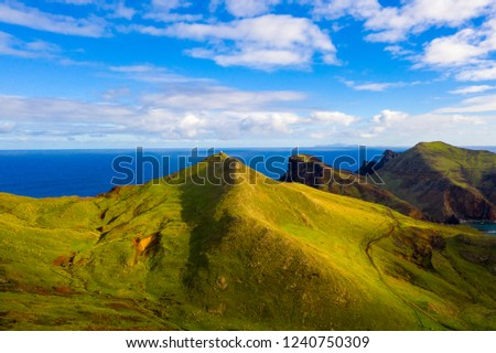 Aerial tropical island view in the middle of the ocean with rocky cliffs and green fields #1240750309