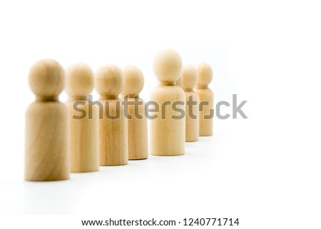 Line of wooden figures, standing out from the crowd and leadership concept. Selective focus on the figurine in front #1240771714