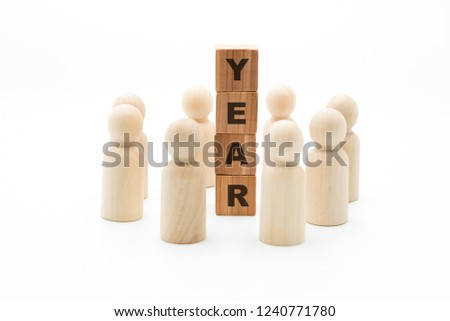 Wooden figures as business team in circle around word YEAR, isolated on white background, minimalist concept #1240771780