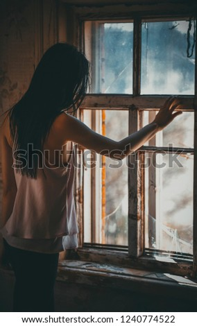 Young girl is standing at the old broken window #1240774522