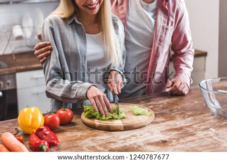 Cropped view of couple preparing salad in kitchen  #1240787677