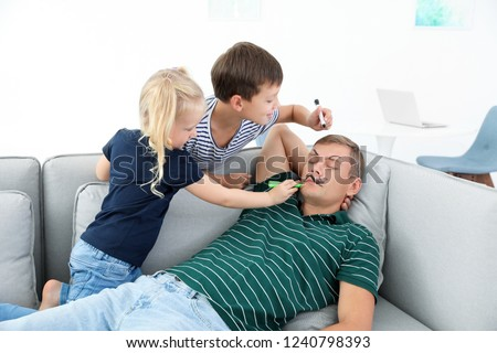 Little children painting their father's face while he sleeping on couch at home. April fool's day prank Royalty-Free Stock Photo #1240798393