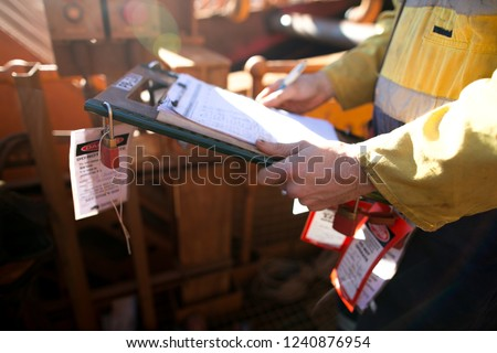 Construction site supervisor inspecting checking names list at safe task isolation procedure permit holder box to ensure all construction miners are locking on correct permit prior to work on site  #1240876954