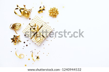 An arrangement of golden Christmas decorations and gift boxes on white background. Flatlay. Copy space #1240944532
