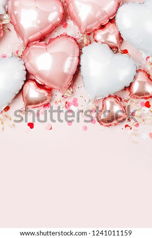 Air Balloons of heart shaped foil  on pastel pink background. Love concept. Holiday celebration. Valentine's Day or wedding/bachelorette party decoration. Metallic balloon #1241011159
