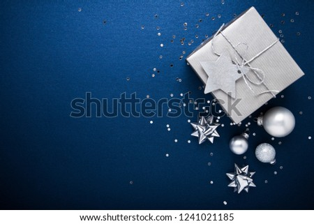Merry Christmas and Happy Holidays greeting card, frame, banner. New Year. Noel. Silver Christmas gifts, ornaments on blue background top view. Winter holiday xmas theme. Flat lay. #1241021185