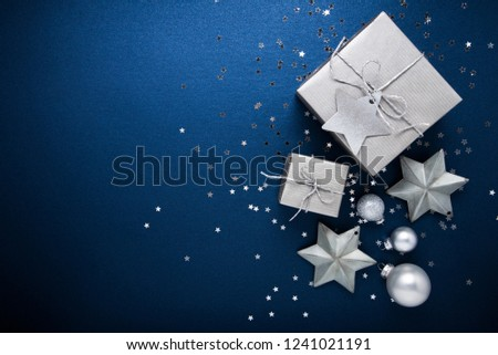 Merry Christmas and Happy Holidays greeting card, frame, banner. New Year. Noel. Silver Christmas gifts, ornaments on blue background top view. Winter holiday xmas theme. Flat lay. #1241021191