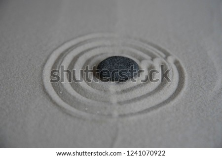 Gray zen stones on the sand with wave drawings. Concept of harmony, balance and meditation, spa, massage, relax #1241070922