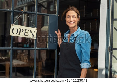 Portrait of a happy waitress standing at restaurant entrance. Portrait of mature business womanattend new customers in her coffee shop. Happy woman owner showing open sign in her small business shop. #1241123071
