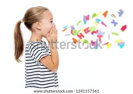 Cute little girl in stripped T-shirt shouting out alphabet letters. Speech therapy concept over white background. Royalty-Free Stock Photo #1241157361