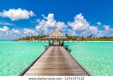 Water Villas (Bungalows) and wooden bridge at Tropical beach in the Maldives at summer day #1241197132