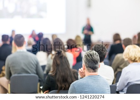 Business and entrepreneurship symposium. Female speaker giving a talk at business meeting. Audience in conference hall. Rear view of unrecognized participant in audience. Copy space on whitescreen. #1241220274