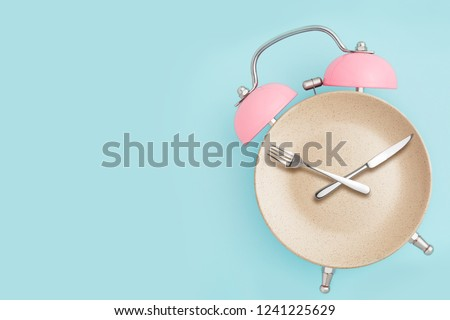 Alarm clock and plate with cutlery . Concept of intermittent fasting, lunchtime, diet and weight loss #1241225629