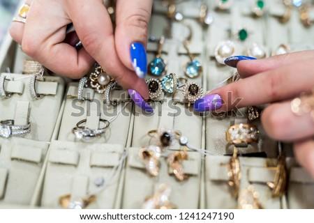 Female hands showing golden jewellery in shop #1241247190