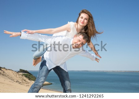 Joyful pretty girl piggybacking on handsome Caucasian boyfriend man playing and having fun in sunny tropical destination for travel holiday #1241292265