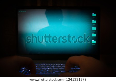 Hacker using laptop. Lots of digits on the computer screen.  #1241331379