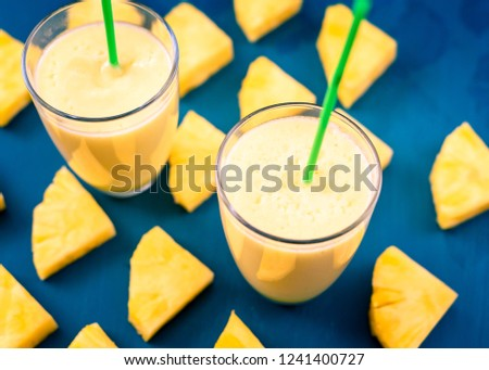 Pineapple smoothie with fresh pineapple on wooden blue table. #1241400727