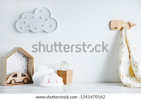 The modern sandinavian newborn baby room with mock up poster frame, wooden car, boxes and clouds. Minimalistic and cozy interior with white walls.