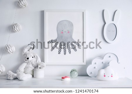 Stylish scandinavian nursery shelf with mock up photo frame, white rabbit and toys. Modern interior with white walls and wooden accessories. #1241470174