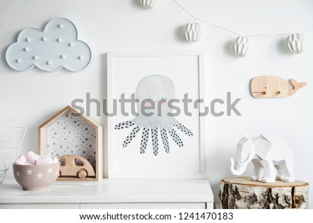 Stylish scandinavian newborn baby room with wooden toys, elephant, cotton lamps and cloud. Modern interior with mock up photo frame. #1241470183