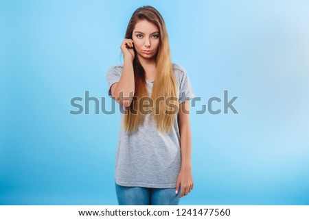 Girl in gray clothes on a blue background touches the ear. Concept attentive, body language, sign, distraction attention. #1241477560